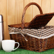 Metal thermos with cup and basket on grass on wooden background — Stock Photo
