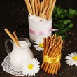 Tasty crispy sticks with pitcher and glass with sour cream on wooden table close-up — Stock Photo #15673321