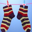 Pair of knit striped socks hanging to dry over blue background — Stock Photo #15673607