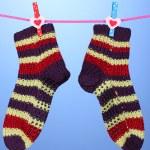 par de tricotar meias listradas pendurado para secar sobre fundo azul — Foto Stock #15673607