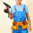 Builder with drill on wall background — Stock Photo