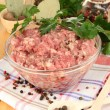 Bowl of raw ground meat with spices on wooden table — Stock Photo #15674263