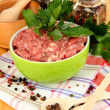 Bowl of raw ground meat with spices on wooden table — Stock Photo