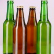Coloured glass beer bottles on purple background — Stock Photo #15674621