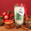 Cookies for Santa: Conceptual image of ginger cookies, milk and christmas decoration on red background — Stock Photo #15674919