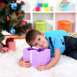 Little boy lying on gift in his hands under Christmas Tree waiting for Santa Claus to come — Stock Photo