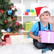 Stock Photo: Child in Santa hat sits near Christmas tree with gift in hands