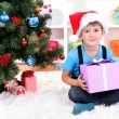 Child in Santa hat sits near Christmas tree with gift in hands — Stock Photo #15675387