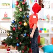 Little boy in Santa hat decorates Christmas tree in room — Stock Photo #15675409