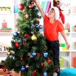 Little boy in Santa hat decorates Christmas tree in room — Stock Photo #15675423