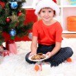 Little boy in Santa hat with milk and cookies for Santa Claus — Stock Photo #15675435