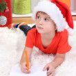 Little boy in Santa hat writes letter to Santa Claus — Stock Photo