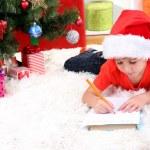 Little boy in Santa hat writes letter to Santa Claus — Stock Photo #15675471