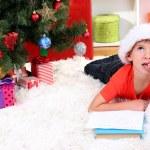 Little boy in Santa hat writes letter to Santa Claus — Stock Photo #15675477