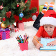Little boy in Santa hat writes letter to Santa Claus — Stock Photo #15675497