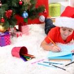 Little boy in Santa hat writes letter to Santa Claus — Stock Photo #15675503