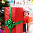 Child in Santa hat near Christmas tree with big gift — Stock Photo #15675511