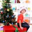 Child in Santa hat near Christmas tree with big gift — Stock Photo #15675515