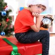 Photo: Little boy with big gift and clock in anticipation of New Year