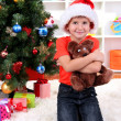 Little boy in Santa hat sits near Christmas tree with gift in hands — Stock Photo #15675549