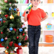 Little boy stands near Christmas tree with badminton rackets — Stock Photo #15675571