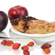 Tasty pie on plate with plums isolated on white — Stock Photo