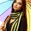 Beautiful young woman with colorful umbrella, close up — Stock Photo