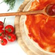 Pizza dough with tomato sauce on wooden board isolated on white — Stock Photo