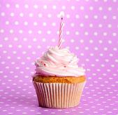 Bizcocho de cumpleaños sabroso con vela, sobre fondo violeta — Foto de Stock
