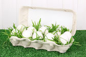 Eco-friendly eggs in box on green grass on wooden background — Stock Photo