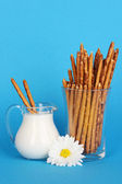 Tasty crispy sticks in glass cup on blue background — Stock Photo