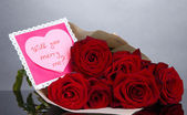 Beautiful bouquet of red roses with valentine on grey background — Photo