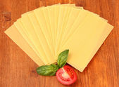 Uncooked lasagna pasta on wooden background — Stock Photo