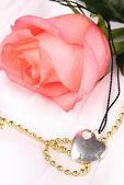 Nabídka růžové růže s srdce přívěsek — Stock fotografie