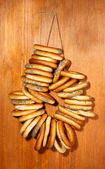 Tasty bagels on rope, on wooden background — Stock Photo