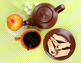Top view of cup of tea and teapot on green tablecloths — Stock Photo