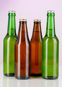 Coloured glass beer bottles on purple background — Stock Photo