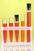 Test-tubes with a colorful solution on green background close-up — Zdjęcie stockowe