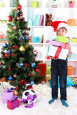 Little boy in Santa hat stands near Christmas tree with gifts — Stok fotoğraf