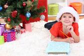 Little boy in Santa hat writes letter to Santa Claus — Stock Photo