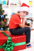 Petit garçon avec grand cadeau et horloge en prévision du nouvel an — Photo