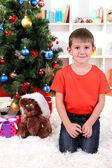 Little boy sits near Christmas tree — Stok fotoğraf