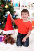 маленький мальчик в шляпе санта сидит возле елки — Стоковое фото