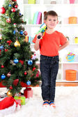 Little boy stands near Christmas tree with badminton rackets — Stok fotoğraf