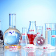 Test-tubes with various acids and chemicals on blue background — Stockfoto