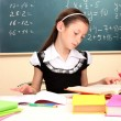 Stock Photo: Beautiful little schoolgirl in classroom reading the book