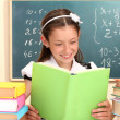 Beautiful little schoolgirl in classroom reading the book — Stock Photo #15735163