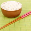 Bowl of rice and chopsticks on bamboo mat — Stock Photo