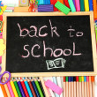 The words &#039;Back to School&#039; written in chalk on the small school desk with various school supplies close-up - Stock Photo