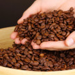 Coffee beans in hands on dark background — Stock Photo #15735923